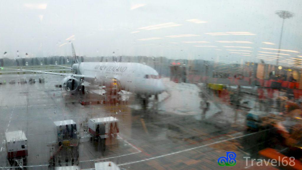 Het vliegtuig van Air New Zealand in de stromende regen op het vliegveld van Singapore